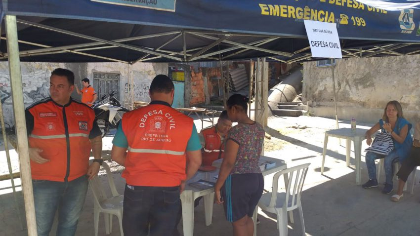 Agentes de Defesa Civil orientando moradora em ação na praça