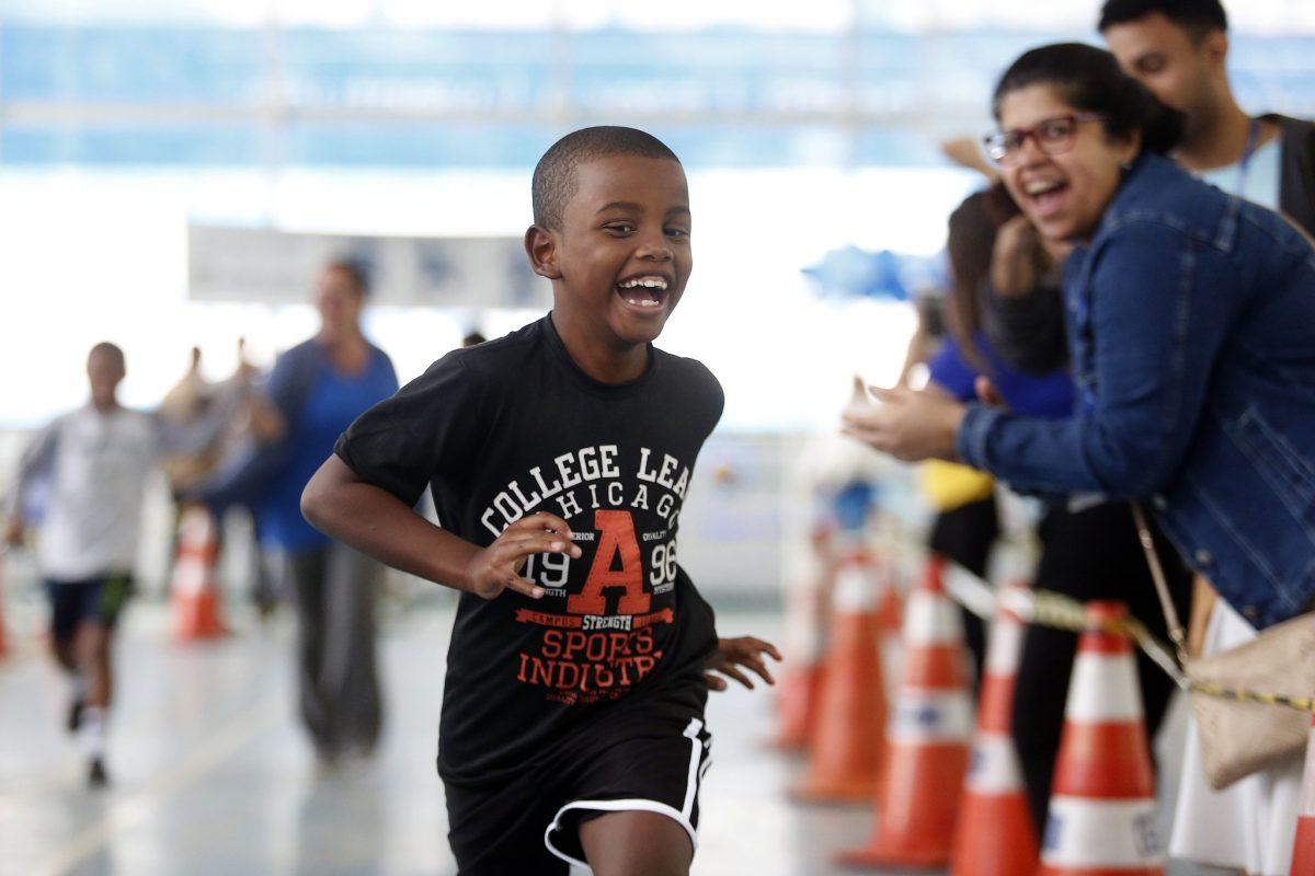 A alegria do menino está estampada no sorriso, ao participar do evento Velozes e Vitoriosos, na Rocinha. Foto: Marcos de Paula / Prefeitura do Rio