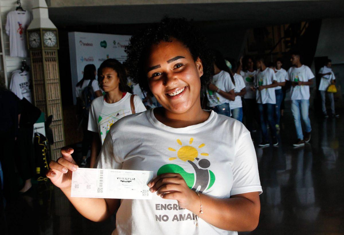 Letícia Ferreira dos Santos, de 17 anos, mostra o sorriso e o ingresso antes da sessão exclusiva do musical Peter Pan, oferecida pelo Cadeira Cativa. Foto: Marcelo Piu / Prefeitura do Rio