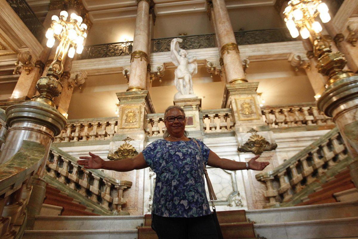 """Kátia Motta, 68 anos, abre os braços na escadaria do Theatro Municipal: """"Eu me sinto uma criança, descobrindo minha cidade"""". Foto: Paulo Sérgio / Prefeitura do Rio"""