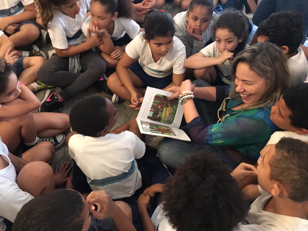 Crianças cercam a jornalista Ana Rebouças para ouvir histórias