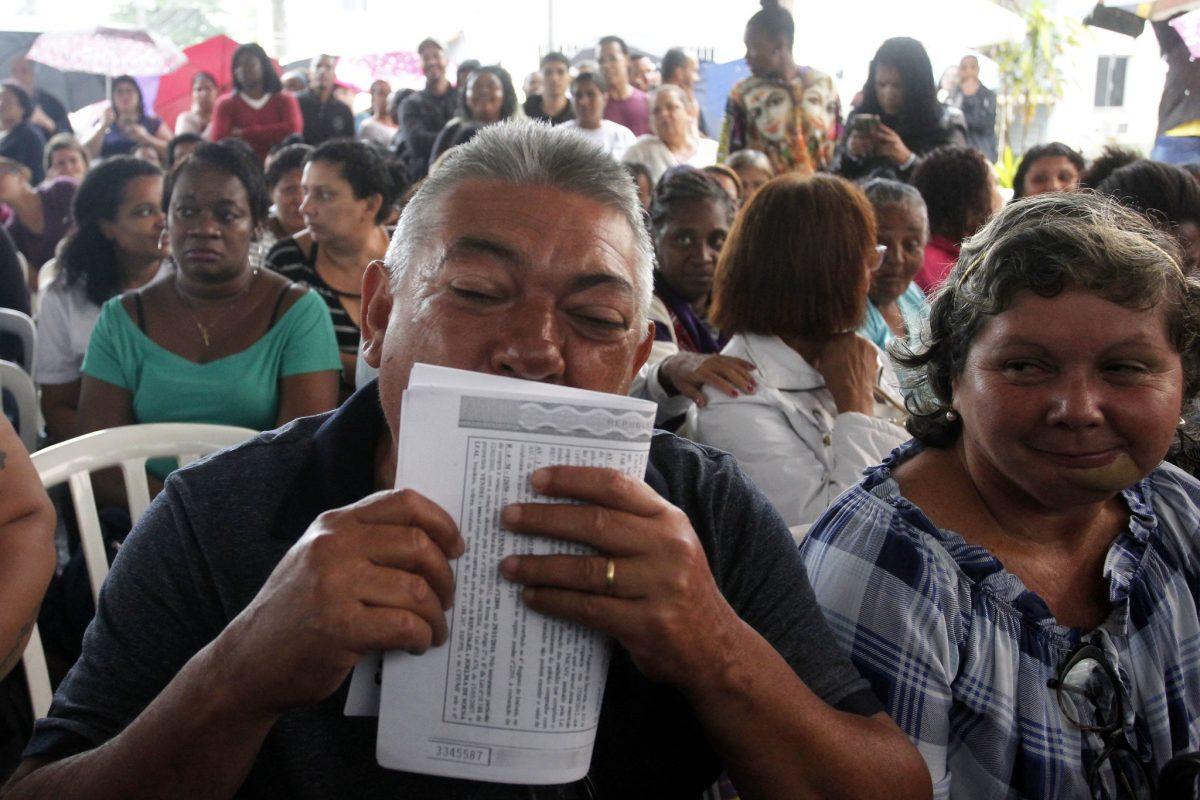 Reginaldo, contemplado com o RGI, beija o documento: fim de um ciclo, e agora proprietário de fato do imóvel onde vive. Foto: Marcelo Piu / Prefeitura do Rio