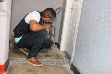 Técnico da Vigilância Sanitária inspeciona ralos da área de serviço de hotel. Foto: divulgação / Subvisa