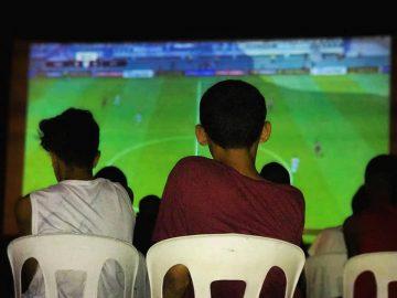 Garotos diante de telão com partida de futebol no videogame. Foto: divulgação