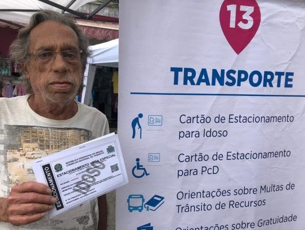 Morador pega cartão de estacionamento para idoso durante o programa Prefeitura Mais Perto de Você, em Padre Miguel