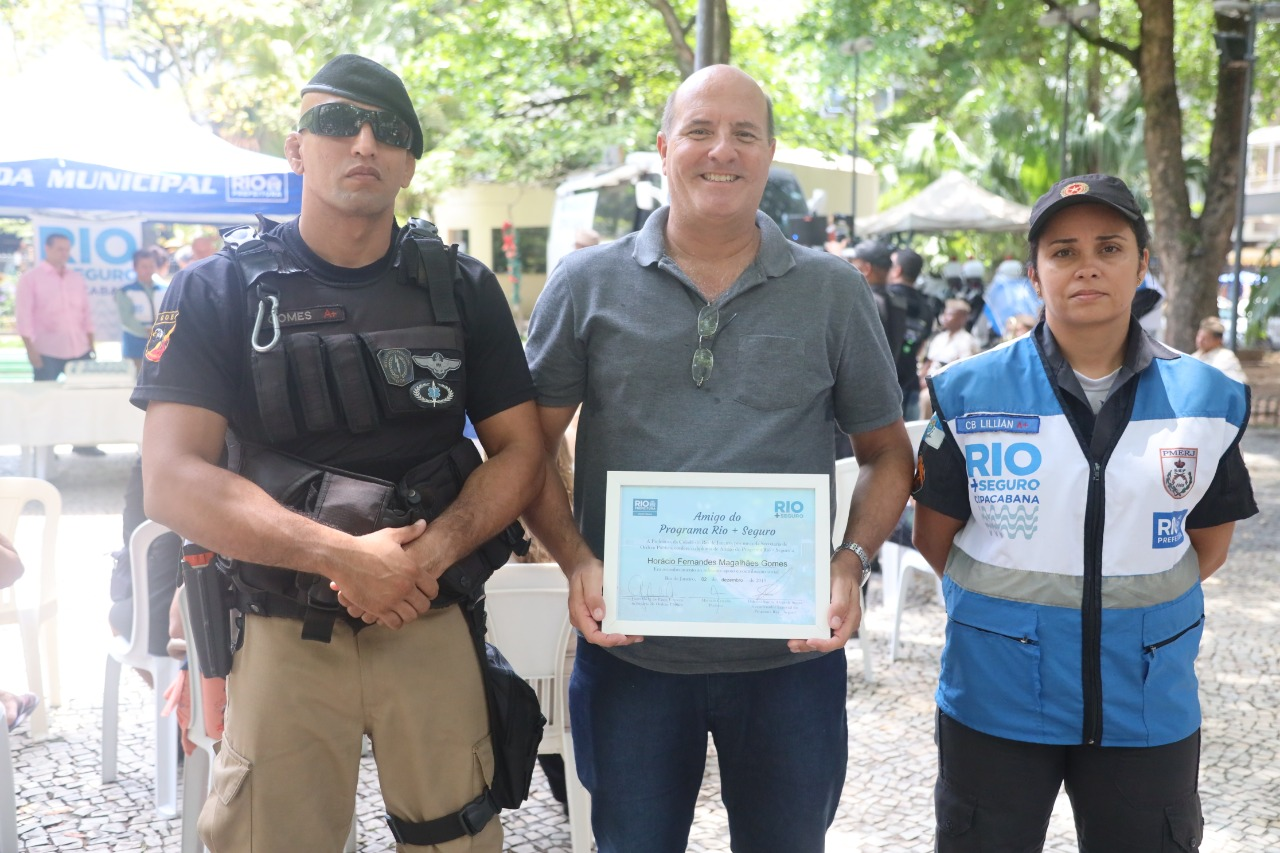Morador de Copabana, Horácio, homenageado pelo Rio+Seguro, faz pose ao lado do GM Gomes e da PM Lilian. Foto: Edvaldo Reis / Prefeitura do Rio