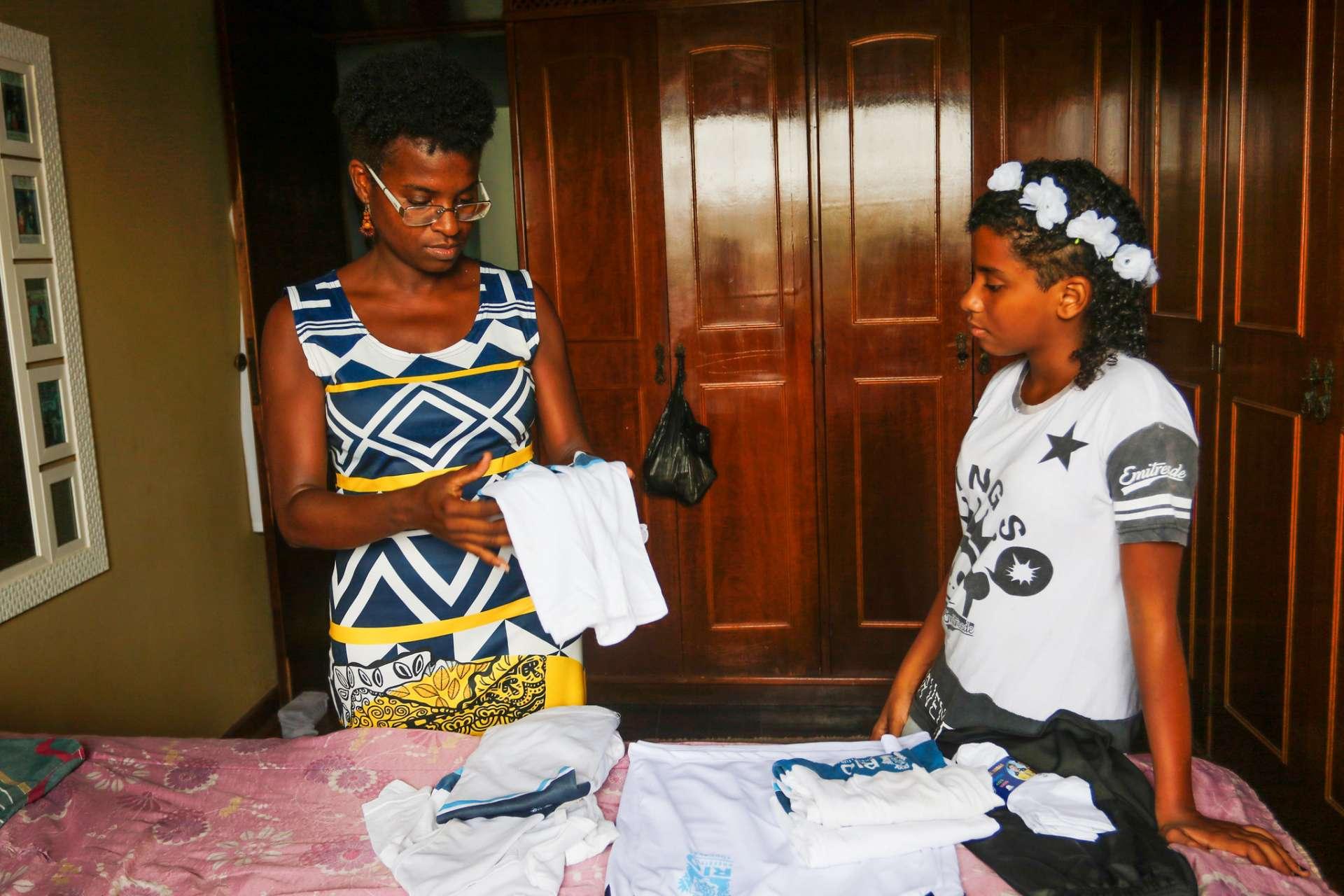 Tatiane e a filha, Swahili, separam camisas do uniforme da rede municipal